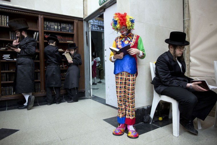 Jewish Ultra-Orthodox men and children wearing costumes, read the Book of Esther, which tells the story of the Jewish festival of Purim, in Bnei Brak, Israel, Wednesday, March 23, 2016. The Jewish holiday of Purim commemorates the Jews' salvation from genocide in ancient Persia, as recounted in the Book of Esther. (AP Photo/Oded Balilty)