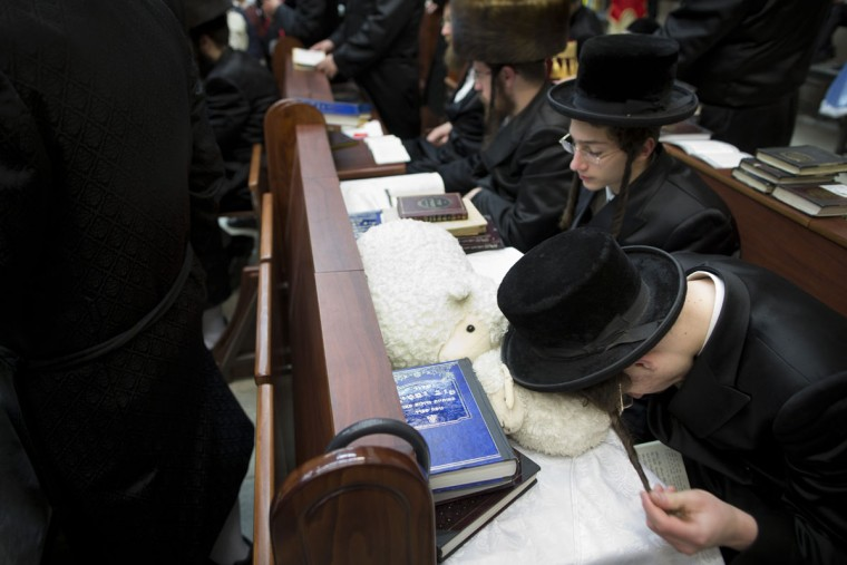 Jewish Ultra-Orthodox men and children, read the Book of Esther, which tells the story of the Jewish festival of Purim, in Bnei Brak, Israel, Wednesday, March 23, 2016. The Jewish holiday of Purim commemorates the Jews' salvation from genocide in ancient Persia, as recounted in the Book of Esther. (AP Photo/Oded Balilty)