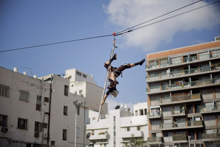 An acrobat performs for foreign migrant workers children to celebrate the Purim festival in Tel Aviv, Israel, Tuesday, March 22, 2016. The Jewish holiday of Purim commemorates the Jews' salvation from genocide in ancient Persia, as recounted in the Book of Esther, which is read in synagogues. Other customs include: sending food parcels and giving charity; dressing up in masks and costumes; eating a festive meal; and public celebrations. (AP Photo/Ariel Schalit)
