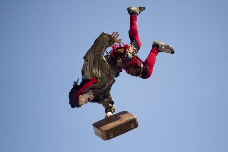 An acrobat jumps from the top of a school building during a performance for foreign migrant workers children to celebrate the Purim festival in Tel Aviv, Israel, Tuesday, March 22, 2016. The Jewish holiday of Purim commemorates the Jews' salvation from genocide in ancient Persia, as recounted in the Book of Esther, which is read in synagogues. Other customs include: sending food parcels and giving charity; dressing up in masks and costumes; eating a festive meal; and public celebrations. (AP Photo/Ariel Schalit)