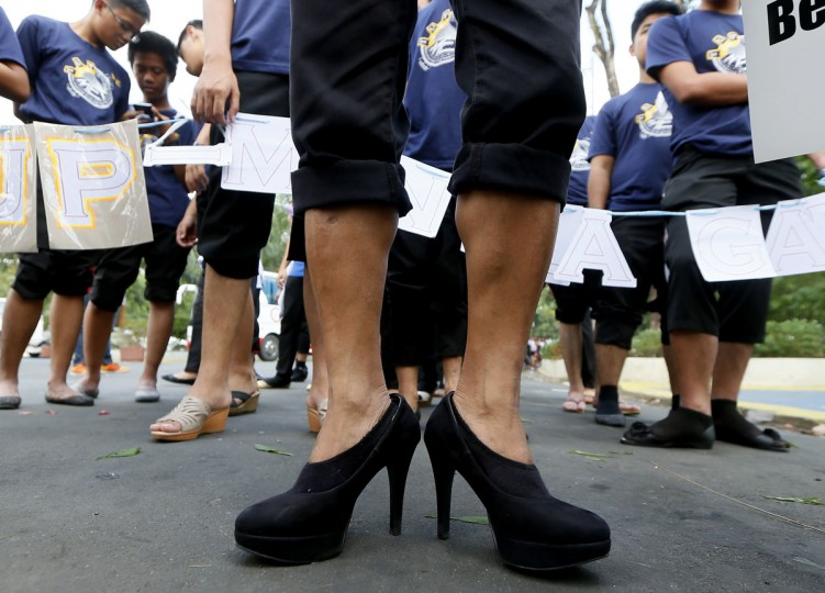 Male students wearing their high-heeled shoes prepare to march around a park to pay tribute to women all over the world on the eve of International Women's Day celebration Monday, March 7, 2016 in suburban Quezon city, northeast of Manila, Philippines. The all male marchers are calling for gender equality and an end to all forms of discrimination and harassment against women. (AP Photo/Bullit Marquez)