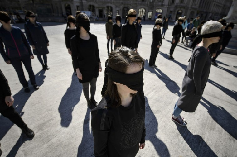 Romanian women activists stand blindfolded with black scarves during a performance honoring the history of feminist movements, marking the International Women's Day in Bucharest, Romania, Tuesday, March 8, 2016. (AP Photo/Andreea Alexandru)