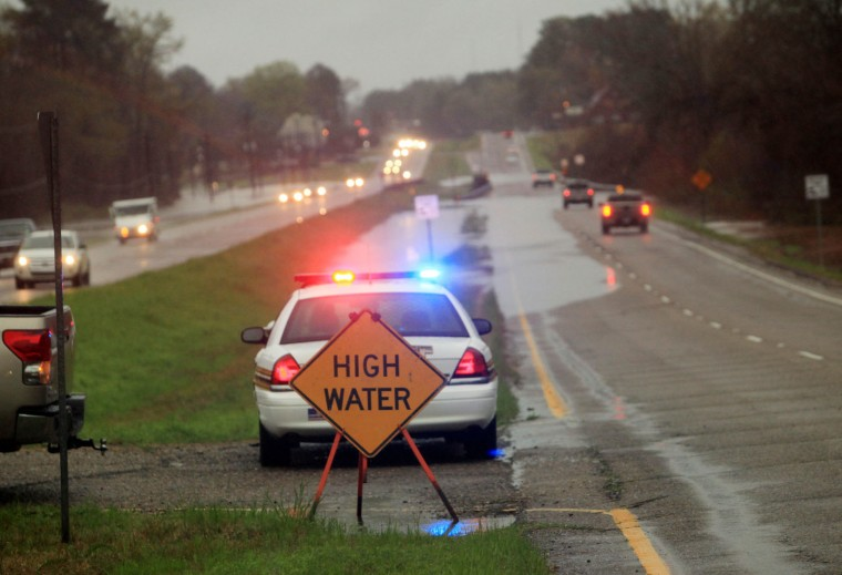 Police monitor floodwaters reaching Highway 80 in Haughton, La., Wednesday, March 9, 2016. Severe thunderstorms have caused major flooding and closed all schools in the area. Several parishes in northwest Louisiana have declared a state of emergency over widespread flooding, and the National Guard is being sent in to help. (AP Photo/Mike Silva)