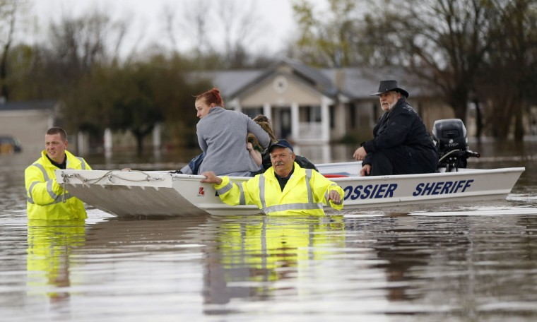 Sarah Yatcko, left, holds her son Tucker Neal as they are evacuated by boat with her father Jim Yatcko, by Bossier County Sheriff personnel during rising floodwaters in Bossier Parish, La., Thursday, March 10, 2016. (AP Photo/Gerald Herbert)