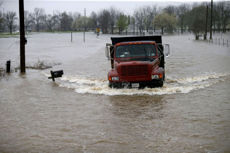 A truck passes through rising floodwaters in Bossier Parish, La., Thursday, March 10, 2016. A second round of rain early Thursday hit an already inundated north Louisiana, where flooding in some places was up to the rooftops and in others submerged cars, stranded families and forced evacuations. (AP Photo/Gerald Herbert)