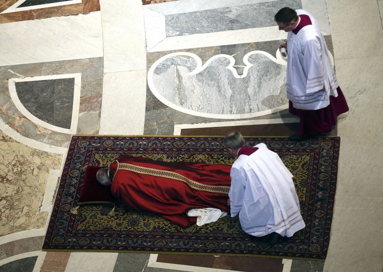 Pope Francis lies on the floor during a mass to celebrate the Lord's Passion, in St. Peter's Basilica at the Vatican Friday, March 25, 2016. (Alessandro Bianchi/Reuters pool via AP Photo)