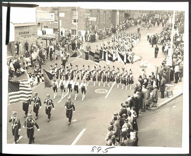 """Big Day for Big Green: Onlookers line both sides of Cathedral street as the Dundalk Drum and Bugle Corps passes Saratoga street during the colorful St. Patrick's Day parade yesterday. Police estimated some 75,000 persons watched the fifty-one marching units."" March, 1965."