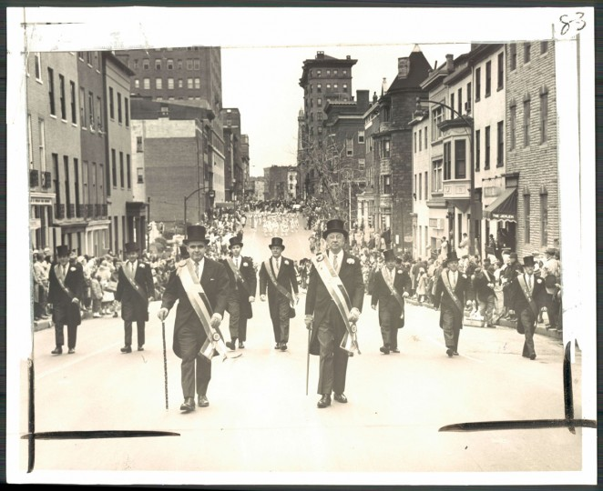 """The Cutaway and Top Hat Crowd -- John J. Sweeney, Jr., general chairman, and William J. Guerin, grand marshall, lead their Irish contemporaries down Cathedral street for the Ancient Order of Hibernians annual St. Patrick's Day Parade."" March, 1964."