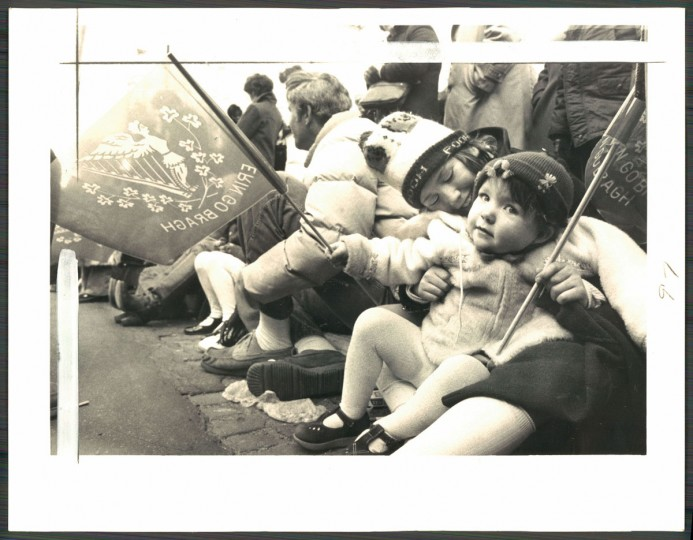 """Snuggled together at their curbside seats, parade celebrants Mary Kathleen Collins, 2, and her sister Noreen, 9, wave Irish flags."" March 1979. (Carter, The Baltimore Sun)."