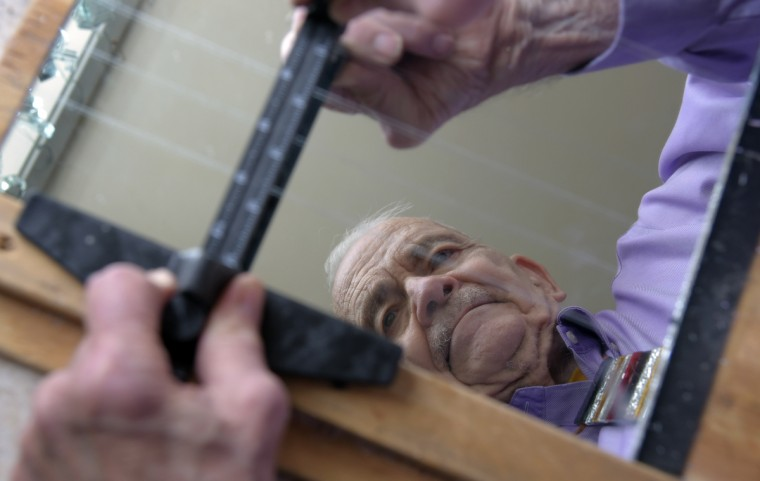 Using a Glastar Circle cutter on a board, Bob Benson scores a sheet of mirror. After seeing a strand of mirrors blowing in the wind twelve years ago, he researched tools online and taught himself how to make mirror art. (Algerina Perna/Baltimore Sun)