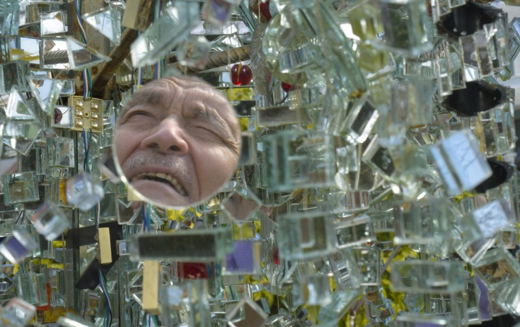 Mirror artist Bob Benson is reflected in one of the mirrors of the tree he created in his yard. Fellow artist and welder Rick Ames created the metal structure for the tree. (Algerina Perna/Baltimore Sun)