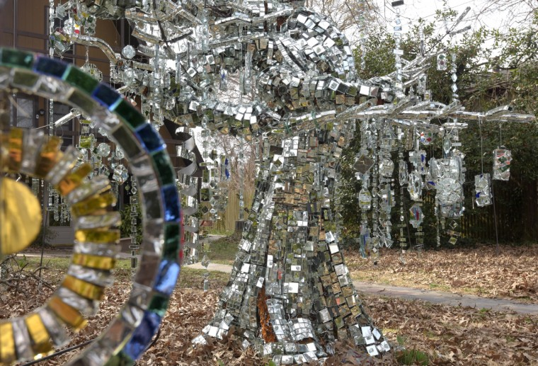 Dripping like icicles, mirrors from one-half to four inches long glued back-to-back dangle from the metal branches in Bob Benson's yard, and clink like a chorus of crystal glasses. (Algerina Perna/Baltimore Sun)