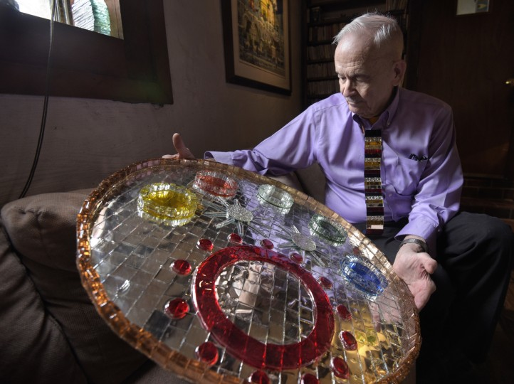 "Bob Benson holds one of his ""mirrorages"" in his living room. Plexiglass is used as a base onto which mirrors are glued flat against its surface. Additional colored and uncolored mirrors are added to make a 3-D design. (Algerina Perna/Baltimore Sun)"