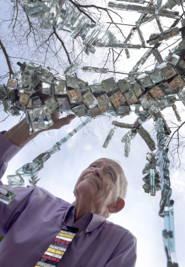 "Bob Benson looks at a limb of one of two man-made ""trees"" in his yard he made of mirrors. The structure for the tree was made by welder and artist Rick Ames. Benson is wearing a tie he made from colored mirrors. (Algerina Perna/Baltimore Sun)"