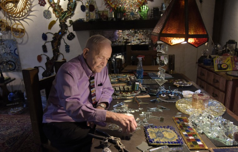 Bob Benson is pictured in his living room, with finished mirror art and pieces of cut mirror, the building blocks of his art. Behind him a tree of colored mirrors snakes up the wall. (Algerina Perna/Baltimore Sun)