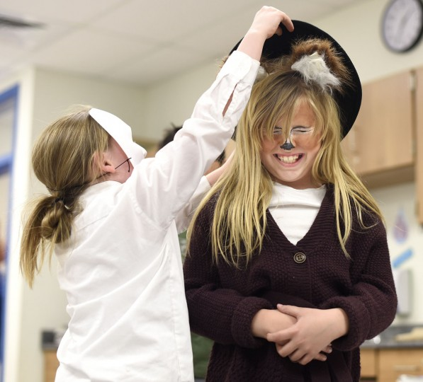 Third grader Layci McGinnis, right, reacts while trying on Alison Stone's costume hat during Read Across America Day at Westminster Elementary School Wednesday, March 2. Children came to school dressed as their favorite story characters.