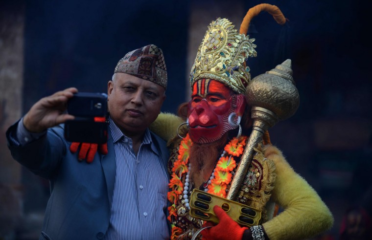 A Nepalese man takes a selfie with a Sadhu (Hindu holy man) dressed as Hanuman, the Monkey God in the Hindu Pantheon at the Pashupatinath temple on the eve of the Hindu festival Maha Shivaratri in Kathmandu on March 6, 2016. Hindus mark the Maha Shivratri festival by offering special prayers and fasting. (PRAKASH MATHEMA/AFP/Getty Images)