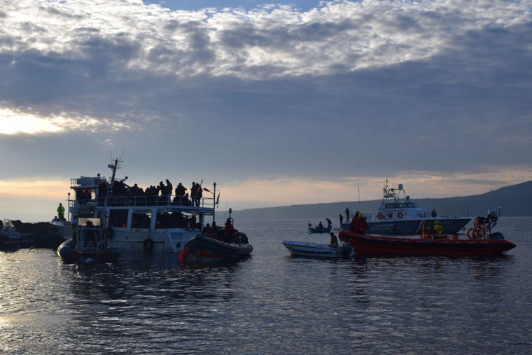 """This small ferry was packed with 180 people from all over the Middle East, South Asia, and Central and Northern Africa. The smuggler had driven them to see but hopped off onto a speedboat before long. The pilotless boat drifted towards Greece and was found by our coalition's lookout teams, and intercepted by a Proactive (Spanish Lifeguards) reduce boat. The Greek Guard, pictured here on the right, threatened the lifeguards with arrest for tying a line to tow the boat, and they subsequently cut the line. Multiple rescue boats, the Coast Guard, and a Portuguese Frontex boat all sat around looking at each other when a Greek fisherman, not caring for the law, pulled up and towed the boat himself. Proactive told me later that they tied that boat after it came within 20 meters of hitting a very dangerous rock near the lighthouse, which would have meant certain death for many of the passengers. Our team handled 3 other boats this night, with the ferry sailing into port at sunrise."" (Ryan Harvey)"