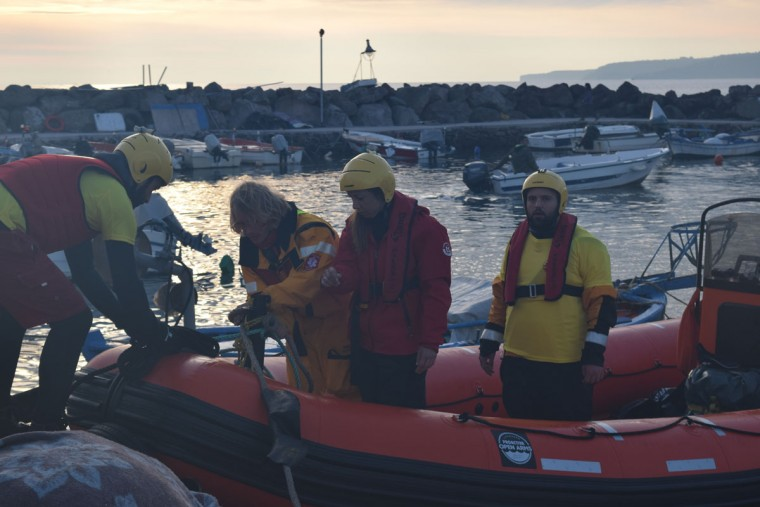 """Members of Proactiva dock during the refugee ferry landing. These amazing people work all night and day in the water, guiding boats to shore and, in the worst cases, doing water rescue during mass-casualty situations. 4 of their members, and a fellow water-rescue volunteer from the Norwegian group Team Humanity, are facing charges for human trafficking for towing a boat a few months ago. The Greek government is accusing them of intervening in a non-emergency situation. The morning of this photo, they did the same again after fears the the ferry would capsize."" (Ryan Harvey)"