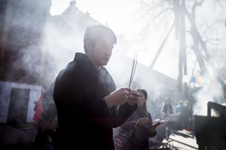 A man holds incense during the Beating Ghost festival at the Yonghe Temple, also known as the Lama Temple, in Beijing on March 8, 2016. The Beating Ghost festival, or Da Gui festival in Chinese, is an important ritual of Tibetan Buddhism and is believed to expel evil spirits and shake off troubles. (FRED DUFOUR/AFP/Getty Images)