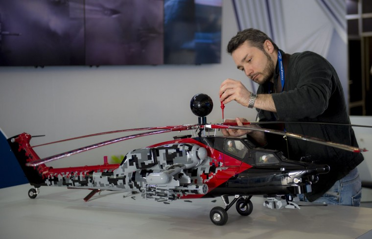 A Russian ground crew member finishes putting together a scale model of a helicopter during the XIX Air and Space Fair (FIDAE) at the international airport in Santiago on March 28, 2016. (MARTIN BERNETTI/AFP/Getty Images)