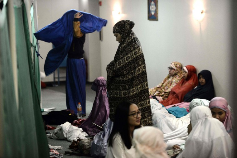 Indonesian Muslims women separated by a curtain from the men at the mosque onboard the cruise ship KM Kelud prepare for the special eclipse prayers, near the island of Belitung in Indonesia on March 9, 2016. (GOH CHAI HIN/AFP/Getty Images)
