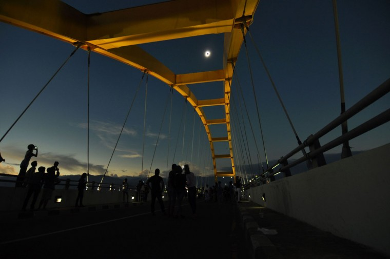 People watch a total total solar eclipse in Palu, Central Sulawesi on March 9, 2016. A total solar eclipse swept across the vast Indonesian archipelago on March 9, witnessed by tens of thousands of sky gazers and marked by parties, Muslim prayers and tribal rituals. (NANANG/AFP/Getty Images)