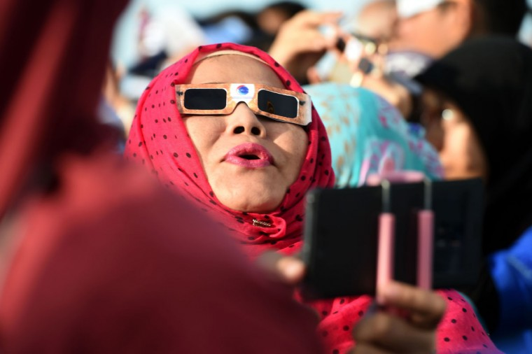 An Indonesian woman joins other passengers to watch the total solar eclipse onboard the cruise ship KM Kelud near the island of Belitung in Indonesia on March 9, 2016. (GOH CHAI HIN/AFP/Getty Images)