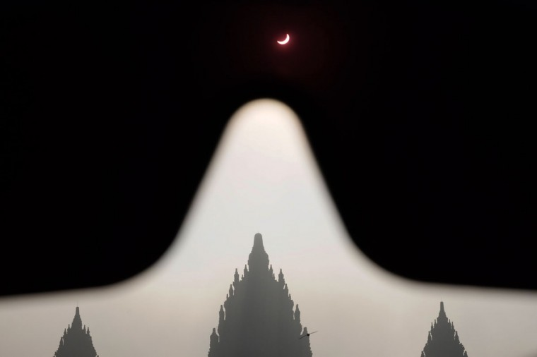 This picture shows a total solar eclipse (top) over the Hindu Prambanan temple in Sleman, Central Java on March 9, 2016. (TARKO SUDIARNO/AFP/Getty Images)