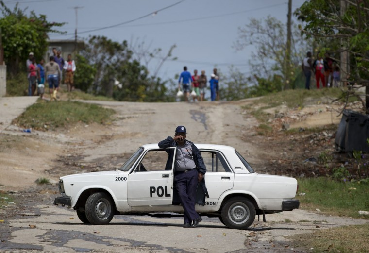Local residents look on from a hilltop as police block off a road outside the Hemmingway House, where U.S. First Lady Michelle Obama was visiting, in the San Francisco de Paula district of Havana, Cuba, Monday, March 21, 2016. (AP Photo/Rebecca Blackwell)
