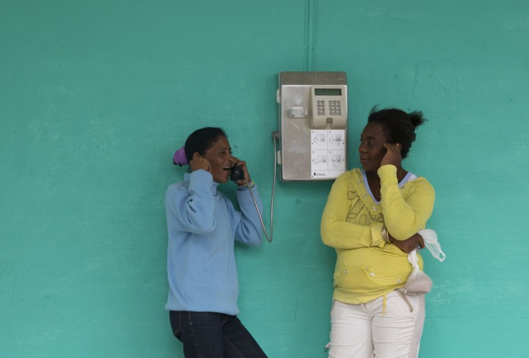 Girls make a call on a pay phone along the route where U.S. First Lady Michelle Obama will pass on her visit to Hemmingway House, in the San Francisco de Paula district of Havana, Cuba, Monday, March 21, 2016. (AP Photo/Rebecca Blackwell)