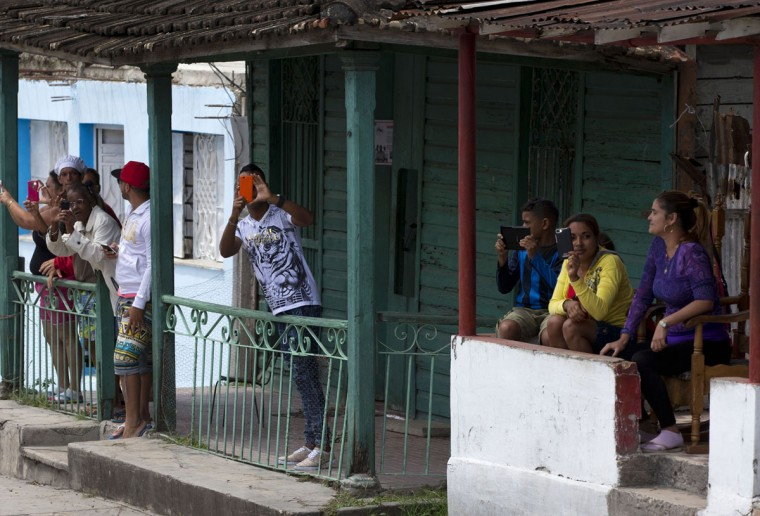 Local residents capture images with their mobile devices, from their front porches as the convoy carrying U.S. First Lady Michelle Obama arrives at Hemmingway House, in the San Francisco de Paula district of Havana, Cuba, Monday, March 21, 2016. (AP Photo/Rebecca Blackwell)