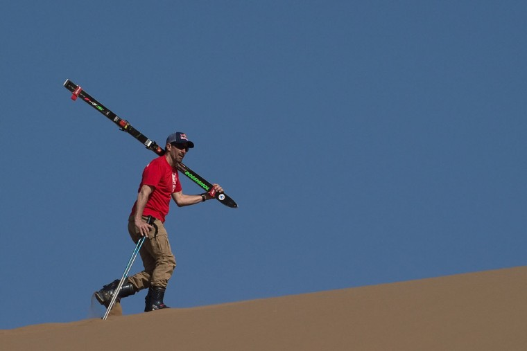 French former overall Ski World Cup winner and race car driver Luc Alphand carries a set of skis up sand dunes during an off-road mapping recognition exercise ahead of the Silk Way Rally 2016 in the Gobi Desert. (NICOLAS ASFOURI/AFP/Getty Images)