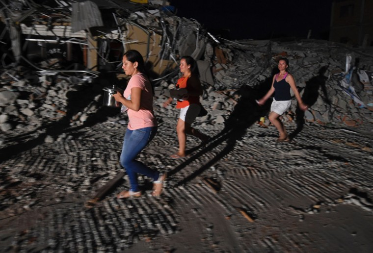 Survivors carry food as they walk past buildings destroyed in the earthquake in Manta on Monday. (LUIS ACOSTA/AFP/Getty Images)