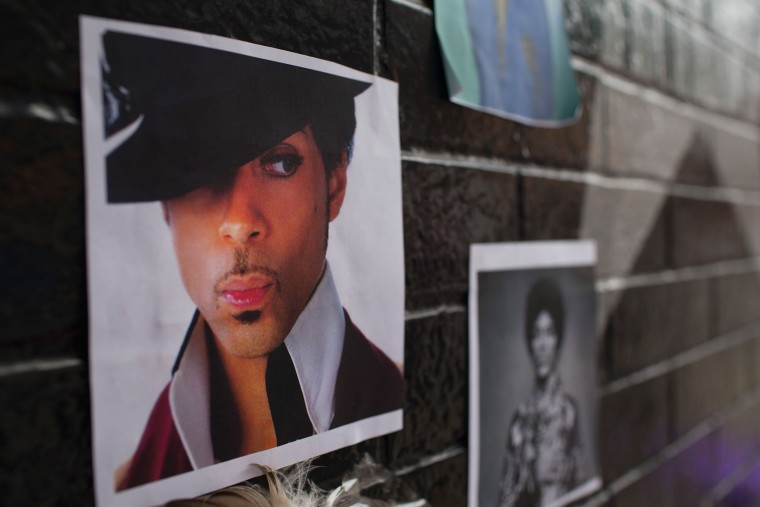 Photos of Prince are attached to the wall outside of the First Avenue nightclub where fans have created a memorial to the artist on April 22, 2016 in Minneapolis, Minnesota. Prince, 57, was pronounced dead shortly after being found unresponsive yesterday at his Paisley Park Studio in Chanhassen, Minnesota near Minneapolis. (Photo by Scott Olson/Getty Images)