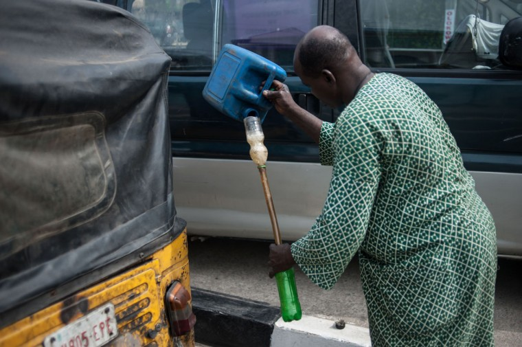 A Tuk tuk driver pours the last of his fuel into a bottle to refill his tank in Lagos on April 6, 2016. Fuel dependant Nigeria has been in the grip of fuel scarcity for the last couple of weeks affecting peoples ability to generate electricity. Due to the fuel scarcity, there has been an increase in the price of goods, commodities and transport fares as well as an increased activity of black market fuel hawkers that sell diluted fuel at extortionate prices. (AFP Photo/Stefan Heunis)