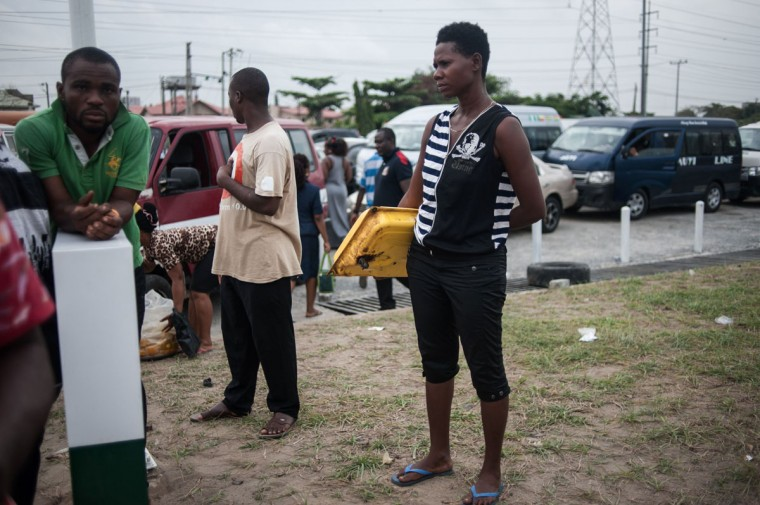 A woman holds the fuel tank of a generator under arm as she waits to buy some fuel in Lagos on April 6, 2016. Fuel dependant Nigeria has been in the grip of fuel scarcity for the last couple of weeks affecting peoples ability to generate electricity. Due to the fuel scarcity, there has been an increase in the price of goods, commodities and transport fares as well as an increased activity of black market fuel hawkers that sell diluted fuel at extortionate prices. (AFP Photo/Stefan Heunis)