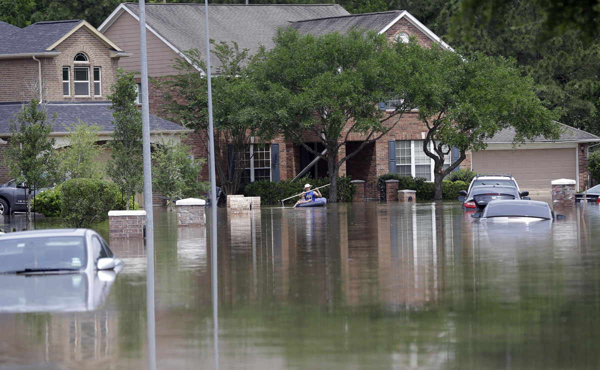 person paddles through a flooded neighborhood tuesday april 19 2016 ...