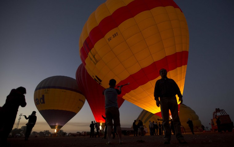 In this Friday, April 1, 2016 photo, tourists watch hot air balloons prepare to take off at dawn, on the west bank of the Nile River in Luxor, Egypt. They take off at first light, providing sky-high views of antiquities below. Luxor in southern Egypt is one of the world's largest outdoor museums, with majestic temples and tombs of ancient kings. (AP Photo/Amr Nabil)