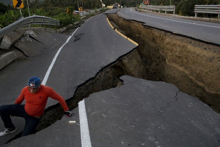 A man jokes around Tuesday after taking some pictures of a section of highway that collapsed due to a 7.8-magnitude earthquake, in Chacras, Ecuador. The strongest earthquake to hit Ecuador in decades flattened buildings and buckled highways along its Pacific coast, sending the Andean nation into a state of emergency. (Rodrigo Abd/AP)
