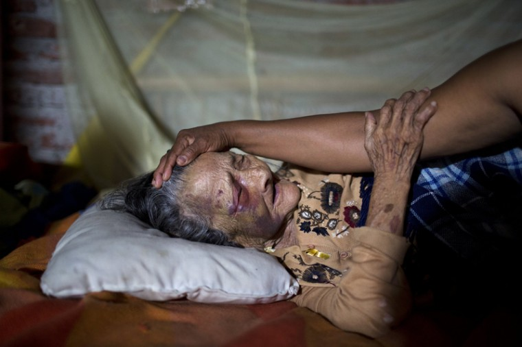 Maria Victoria, 89, is comforted by her daughter Mariana in Estancia Las Palmas, Ecuador, on Tuesday. Maria Victoria was injured when a column fell on her after a 7.8-magnitude earthquake collapsed her home. (Rodrigo Abd/AP)