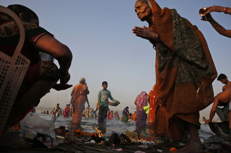 An elderly Indian Hindu devotee performs morning rituals on the banks of the Ganges River on the first day of the nine-day Hindu festival of Navratri, in Allahabad, India, Friday, April 8, 2016. Navaratri lasts for nine days, with three days each devoted to the worship of the goddess of valor Durga, the goddess of wealth Lakshmi, and the goddess of knowledge Saraswati. (AP Photo/Rajesh Kumar Singh)