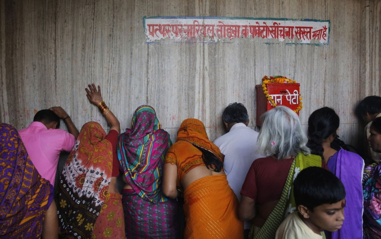 Indian Hindu devotees pray against the wall of a temple on the first day of the nine-day Hindu festival of Navratri, in Allahabad, India, Friday, April 8, 2016. Navaratri lasts for nine days, with three days each devoted to the worship of the goddess of valor Durga, the goddess of wealth Lakshmi, and the goddess of knowledge Saraswati. (AP Photo/Rajesh Kumar Singh)