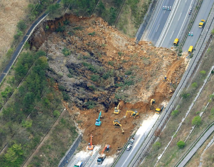 Heavy machinery works recovery efforts of Oita Expressway damaged by a landslide following an earthquake in Yufu, Oita prefecture, Japan, Saturday, April 16, 2016. Powerful earthquakes shook southwestern Japan, trapping many others beneath flattened homes and sending thousands of residents to seek refuge in gymnasiums and hotel lobbies. (Sadayuki Goto/Kyodo News via AP)