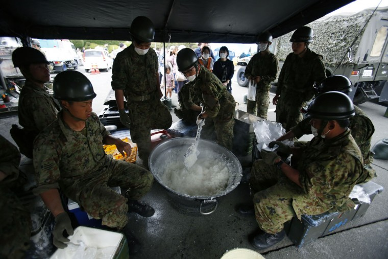 Members of Japan Self-Defence Forces cook rice for local residents at a distribution center in Mashiki, Kumamoto prefecture, southwestern Japan, Saturday, April 16, 2016. Two powerful earthquakes a day apart shook southwestern Japan, killing a number of people, injuring more and trapping many beneath flattened homes and sending thousands to seek shelter in gymnasiums and hotel lobbies. (AP Photo/Koji Ueda)