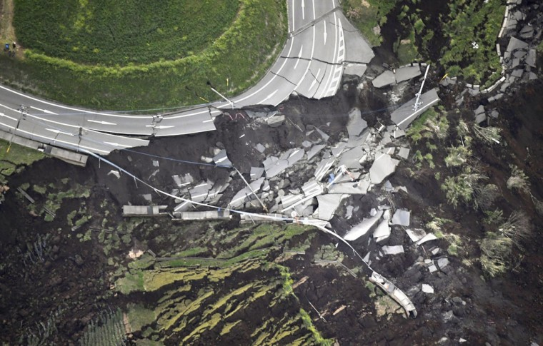 In this aerial photo, the landslide caused by the earthquake disrupts the road in Minamiaso town, Kumamoto prefecture, southern Japan Saturday, April 16, 2016. A powerful earthquake struck southern Japan early Saturday, barely 24 hours after a smaller quake hit the same region. (Kyodo News via AP)