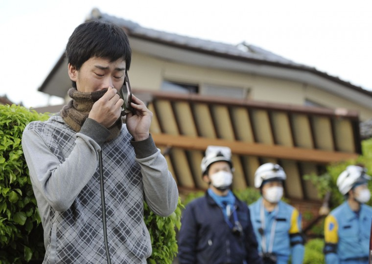 A man cries as he talks with his sister on a mobile phone while an operation to rescue their father is continued in Mashiki, Kumamoto prefecture, southern Japan Saturday, April 16, 2016. A powerful earthquake struck southern Japan early Saturday, barely 24 hours after a smaller quake hit the same region. (Ryosuke Uematsu/Kyodo News via AP)