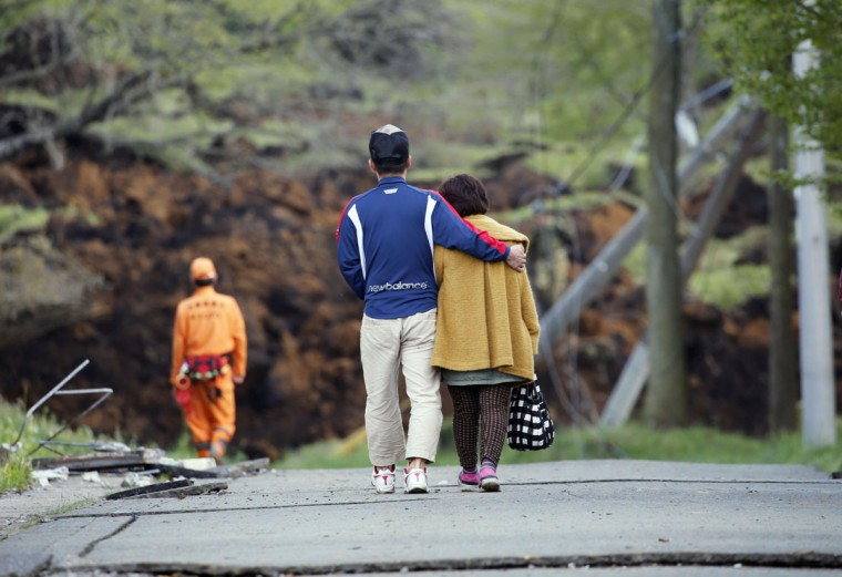 A man hugs his mother as they leave their house buried in a landslide caused by earthquakes in Minamiaso, Kumamoto prefecture, Japan, Sunday, April 17, 2016. Two nights of increasingly terrifying earthquakes flattened houses and triggered major landslides in southern Japan. (Yuki Sato/Kyodo News via AP)