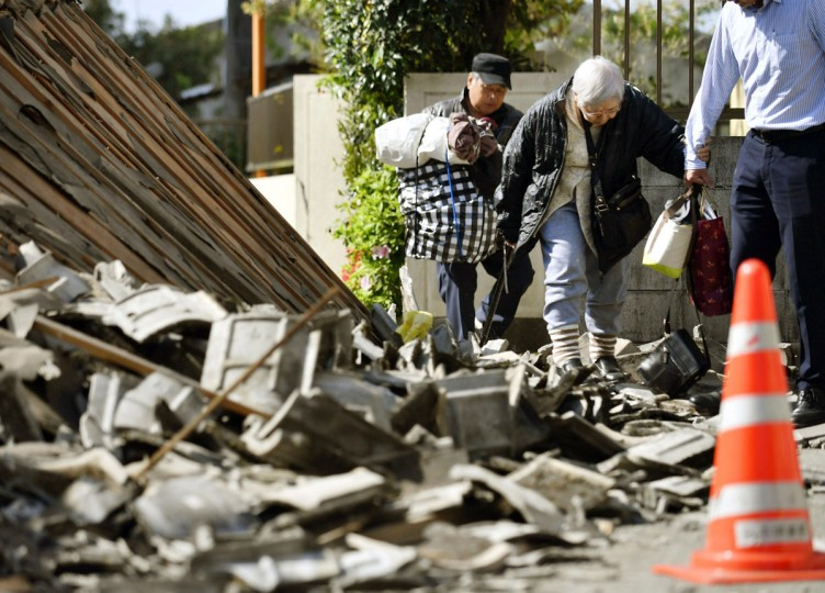 Residents walk through debris from houses destroyed by Thursday's earthquake to evacuate in Mashiki, Kumamoto prefecture, southern Japan, Friday, April 15, 2016. The powerful earthquake struck Thursday night, knocking down houses and buckling roads. (Yu Nakajima/Kyodo News via AP)