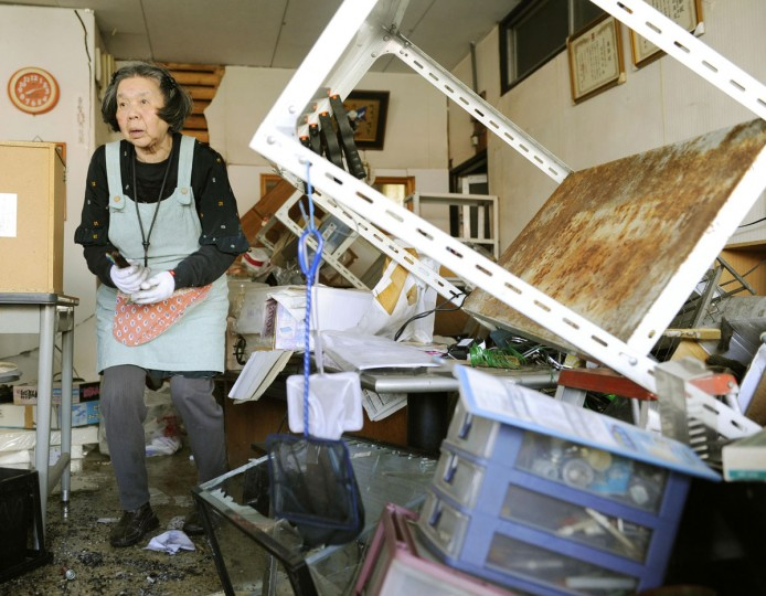 A woman cleans her store destroyed by Thursday's earthquake, in Mashiki, southern Japan, Friday, April 15, 2016. The strong earthquake toppled houses and buckled roads in southern Japan. (Ryosuke Uematsu/Kyodo News via AP)